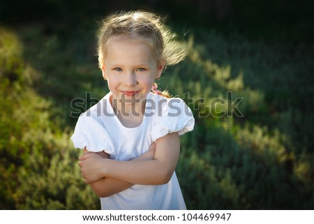 Closeup portrait of a smiling child outdoor over summer grass background