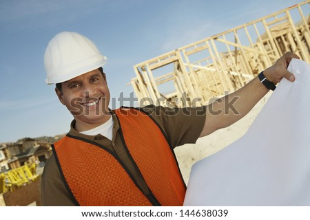 Closeup portrait of a smiling construction worker with blueprints - stock photo