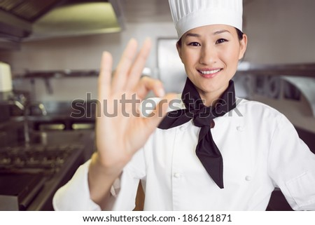 Closeup portrait of a smiling female cook gesturing okay sign in the kitchen - stock photo