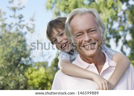 Closeup portrait of a smiling grandfather with grandson riding piggyback outdoors - stock photo