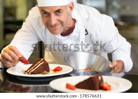 Closeup portrait of a smiling male pastry chef decorating dessert in the kitchen - stock photo