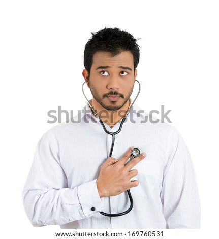 Closeup portrait of a smiling man, business person, worker listening to his heart with stethoscope isolated on a white background. Preventive medicine or financial health condition concept. - stock photo
