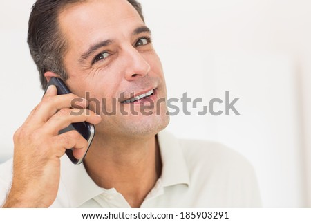 Closeup portrait of a smiling man using mobile phone over white background
