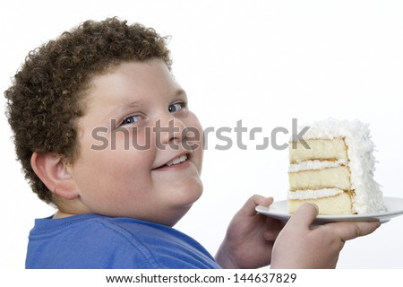 Closeup portrait of a smiling overweight boy holding large slice of cake - stock photo