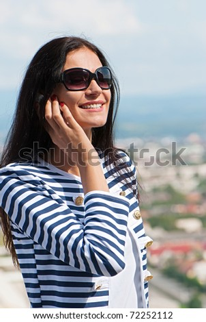 Closeup portrait of a smiling young beautiful woman talking on cellphone - stock photo