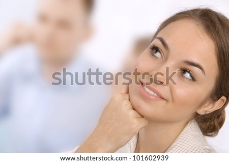Closeup portrait of a smiling young business executive in a meeting with colleagues - stock photo