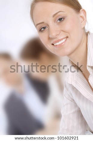 Closeup portrait of a smiling young business woman in a meeting with colleagues - stock photo