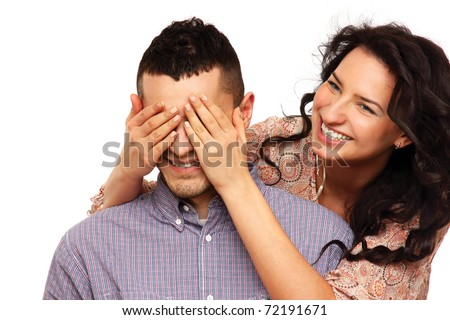 Closeup portrait of a smiling young woman covering her husband eyes to surprise him - stock photo