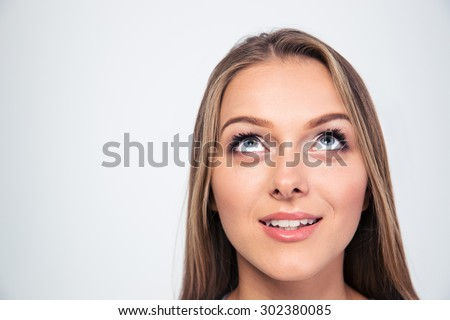 Closeup portrait of a smiling young woman looking up isolated on a white background - stock photo