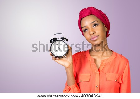 Closeup portrait of a stressed woman holding, looking anxiously at a clock - stock photo