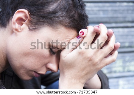 Closeup portrait of a stressed woman in a deep pain. Her face is pressed against her hands. - stock photo