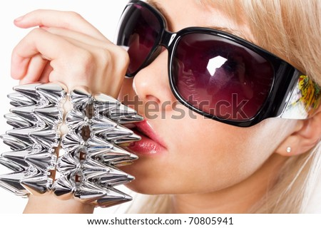Closeup portrait of a stunning young female fashion model wearing spike bracelet and sunglasses - stock photo