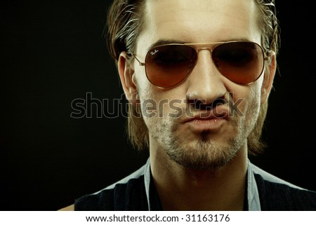 Closeup portrait of a stylish sneering man in sunglasses on black
