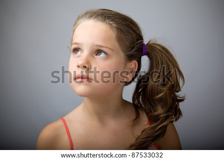 Closeup portrait of a sweet child looking up against grey background - stock photo