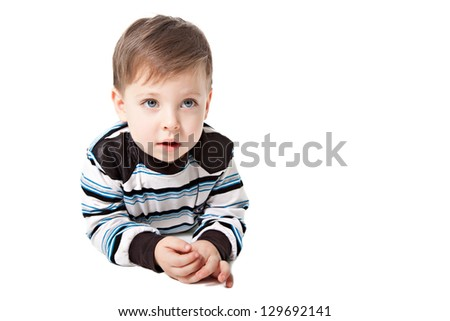 Closeup portrait of a sweet little adorable child lying on floor over white background - stock photo