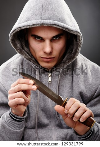Closeup portrait of a threatening mafia man, holding a knife in his hands, over gray background, representing the concept of danger - stock photo