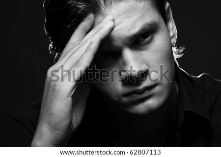 Closeup portrait of a upset young man with hand on his head - stock photo