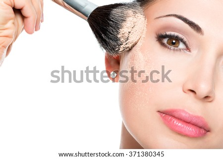 Closeup portrait of a woman  applying dry cosmetic tonal foundation  on the face using makeup brush.  - stock photo