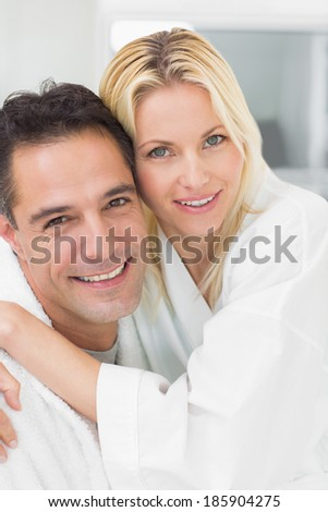 Closeup portrait of a woman embracing man in the kitchen at home - stock photo