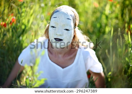 Closeup portrait of a woman hiding her face behind oriental mask smiling - stock photo