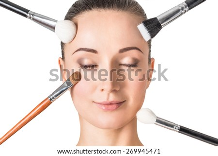 Closeup portrait of a woman with make-up brushes. - stock photo