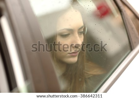 Closeup portrait of a worried car passenger looking at side through the window in a sad rainy day - stock photo