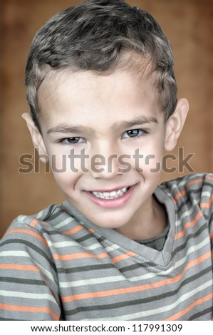 Closeup portrait of a 5 year old boy looking at the camera and smiling - stock photo