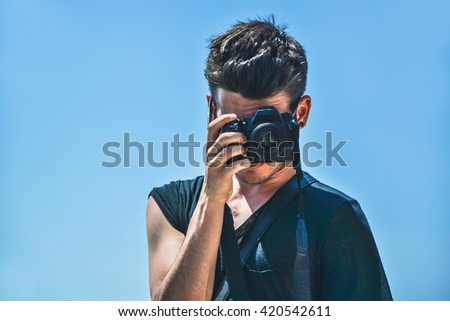 Closeup portrait of a young and caucasian man taking a picture - lifestyle, people and technology concept - stock photo