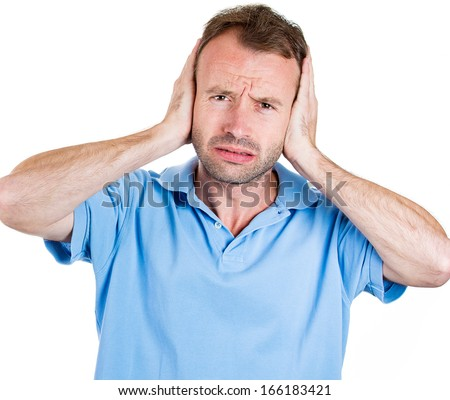 Closeup portrait of a young angry unhappy stressed man covering his ears looking at you camera, stop making that loud noise it's giving me a headache, isolated on white background. Negative emotion - stock photo