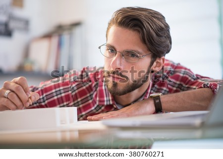 Closeup, portrait of a young architect working on a building project, he has a beard and glasses - stock photo