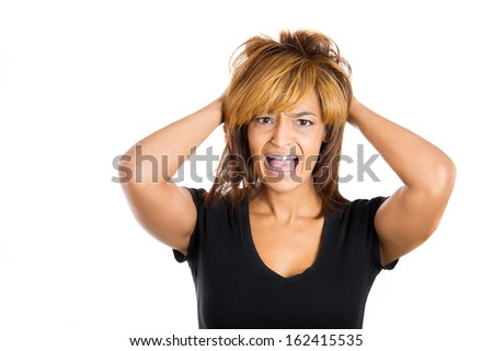 Closeup portrait of a young, attractive stressed woman who is going crazy pulling her hair out with hands in frustration, isolated on a white background. Negative human emotions facial expressions. - stock photo