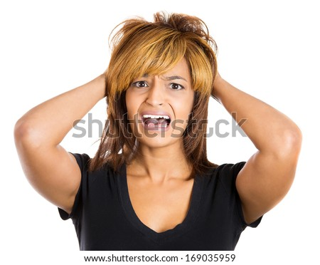 Closeup portrait of a young, attractive stressed woman who is going crazy pulling her hair out with hands in frustration, isolated on a white background. Negative human emotions facial expressions.
