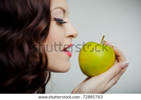 Closeup portrait of a young beautiful girl making a bite on green apple standing on half-face - stock photo