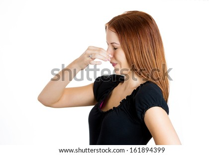 Closeup portrait of a young beautiful woman who covers her nose, looks away, something stinks, very bad smell, situation, isolated on white background with copy space. Human facial expressions - stock photo