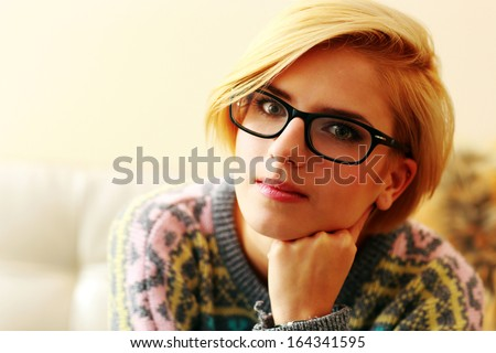 Closeup portrait of a young blonde woman in glasses - stock photo