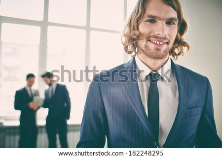 Closeup portrait of a young businessman smiling and posing at camera on the foreground  - stock photo