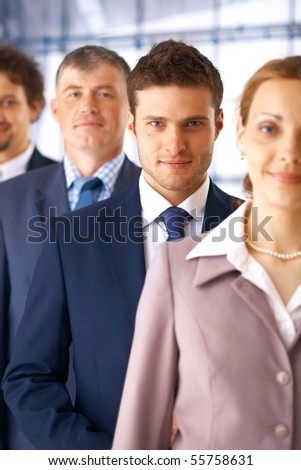 Closeup portrait of a young businessman standing in the row with his colleagues. - stock photo