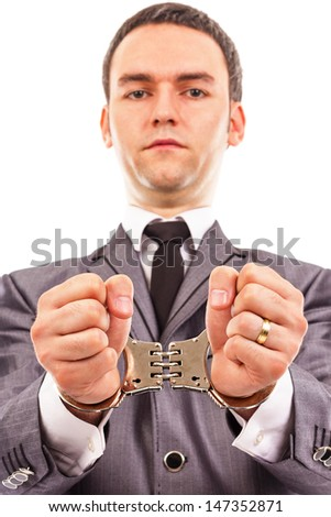 Closeup portrait of a young businessman with handcuffed hands. White background - stock photo