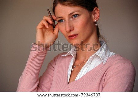 Closeup portrait of a young businesswoman lost in thoughts with a pen in hand - stock photo