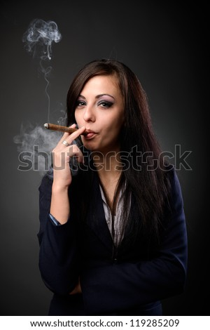 Closeup portrait of a young businesswoman smoking cigar and blowing smoke, on dark background - stock photo