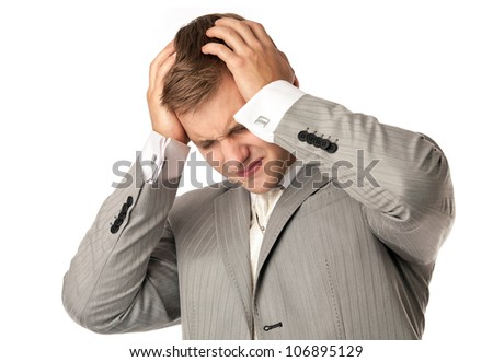 Closeup portrait of a young Caucasian man holding his head in despair, isolated over white - stock photo