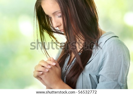 Closeup portrait of a young caucasian woman praying, against abstract green background - stock photo