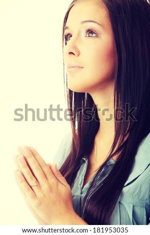 Closeup portrait of a young caucasian woman praying isolated on white background