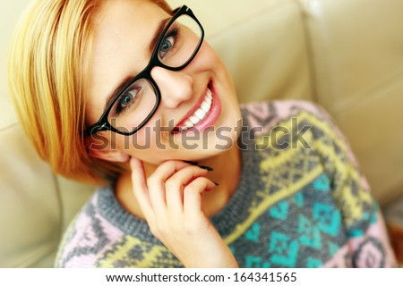 Closeup portrait of a young cheerful woman in glasses  - stock photo