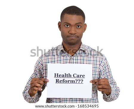 Closeup portrait of a young confused skeptical man holding a sign health care reform, hoping for universal health care coverage, isolated on a white background. politics, government , legislation - stock photo