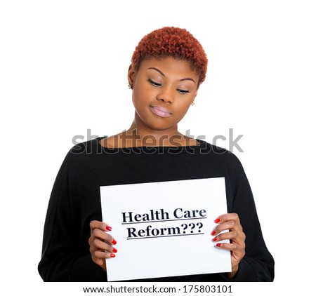 Closeup portrait of a young confused skeptical woman holding a sign health care reform, uncertain of universal insurance coverage, isolated on a white background. politics, government , legislation - stock photo