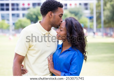 Closeup portrait of a young couple, guy holding woman and kissing face, happy moments, positive human emotions on isolated outdoors outside park background. - stock photo
