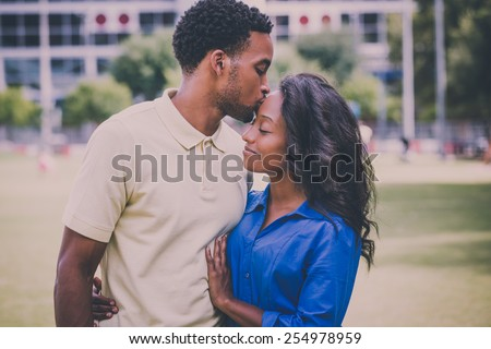 Closeup portrait of a young couple, guy holding woman and kissing face, happy moments, positive human emotions on isolated outdoors outside park background. Retro faded vintage look - stock photo