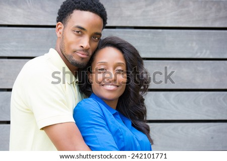 Closeup portrait of a young couple, guy in yellow shirt holding woman with blue shirt from behind, happy moments, positive human emotions on isolated stripe wood board background. - stock photo