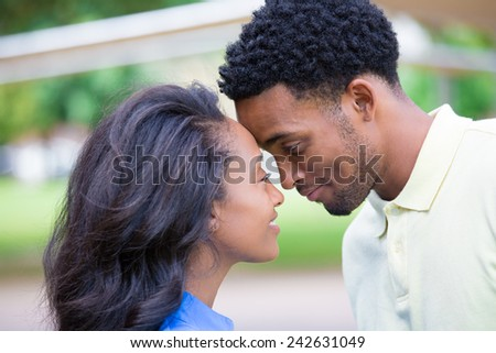 Closeup portrait of a young couple, guy in yellow shirt looking into woman's eyes with blue shirt, head to head, happy moments, positive human emotions, isolated outside outdoors background - stock photo